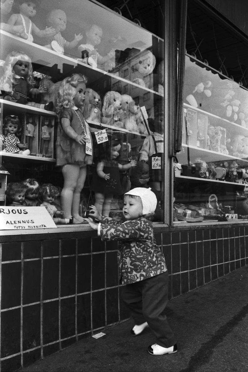 Neljäs linja 2. Pieni tyttö katselemassa lelukauppa Peter Panin näyteikkunassa olevia suuria ...